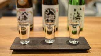 A row of glasses containing sake with the bottles in the background