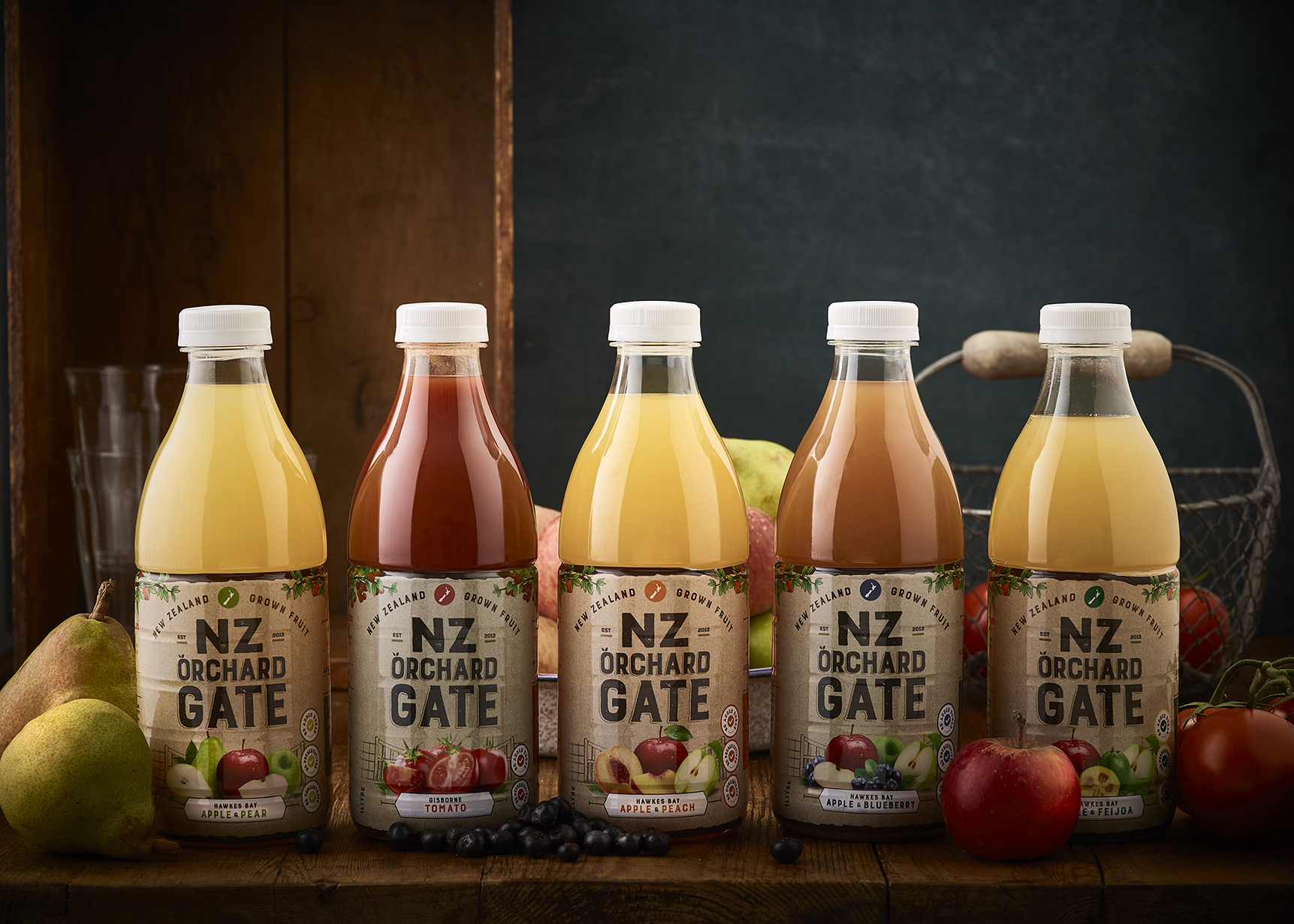 orchard gate juices lined up on a wooden table, surrounded by fruit