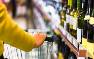 a shopper considers buying wine