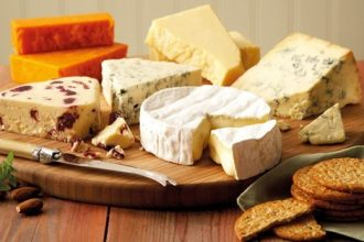 nzsca promotional image: several wedges and wheels of cheese. a camembert, a brie, a blue, and a cheddar are immediately obvious but there are a few other cheeses.