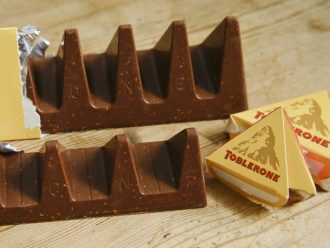 In this photo illustration two bars of the Toblerone Swiss chocolate are shown, at front is the new style 150 gram bar showing the reduction in triangular pieces, in the background is the older style 360 gram bar, pictured in London, Tuesday, Nov. 8, 2016. More valleys, fewer chocolate peaks: The maker of Toblerone Swiss chocolate says it's widened the spaces in its iconic, triangle-array bars for some discount shops in Britain to keep prices down. Mondelez International says the move aims to meet pricing targets by customer Poundland and other discount retailers, and has nothing to do with Britain's vote to leave the European Union.
