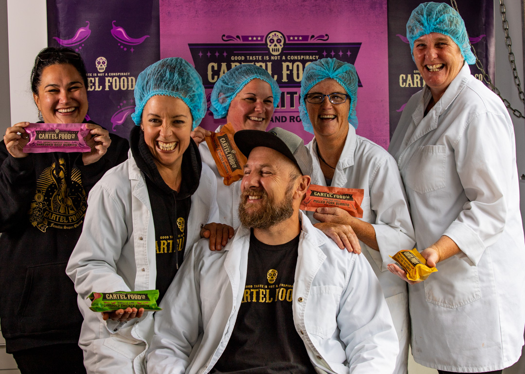 Five women and one man wearing shower caps and white lab coats