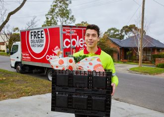 Coles delivery service worker holding grocery parcel