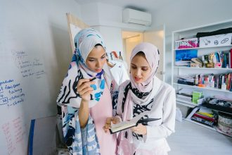 Hijabi women looking at notepad
